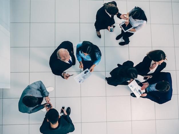 Un grupo de empleados discutiendo datos financieros.