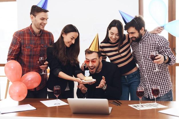 Un grupo de empleados de oficina celebran el cumpleaños de la empresa.
