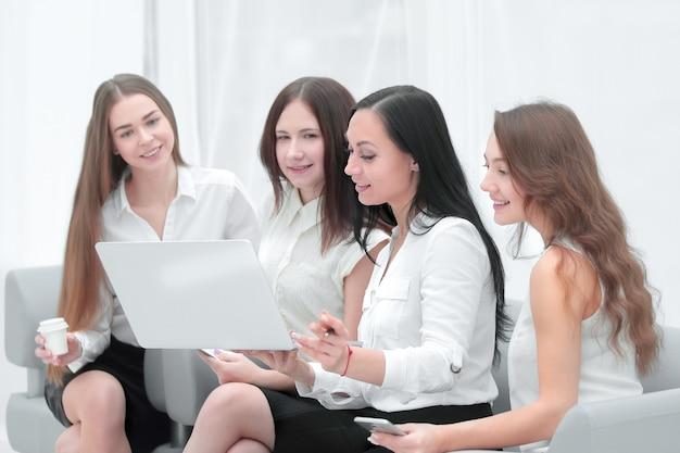 Grupo de empleados que utilizan la computadora portátil para verificar los datos financieros.