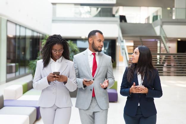Grupo empresarial con celulares discutiendo proyecto