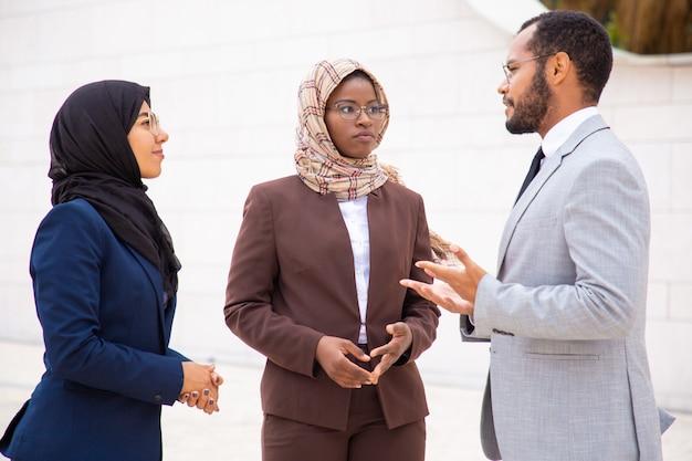 Grupo empresarial diverso discutiendo proyecto afuera