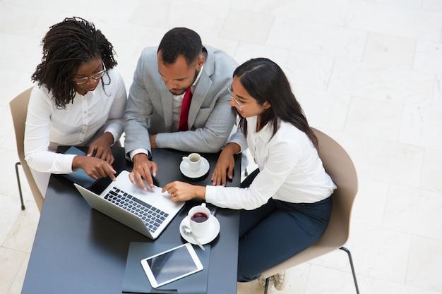 Grupo empresarial diverso que trabaja en la computadora portátil