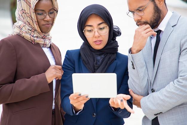 Grupo empresarial diverso serio que mira y discute contenido