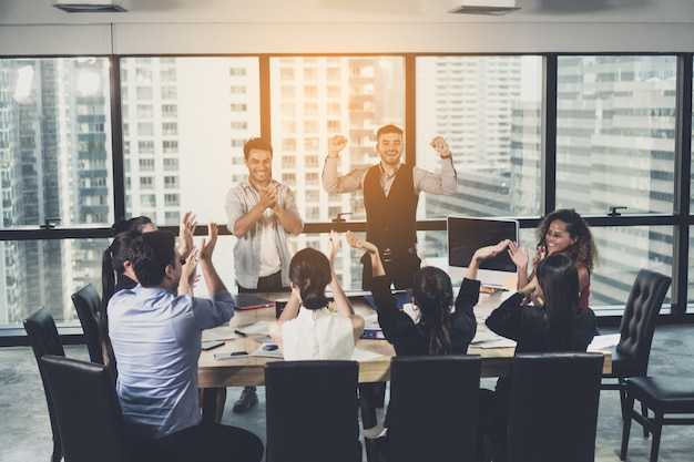 Grupo empresarial exitoso celebrando en la sala de reuniones. negocios, personas, éxito y concepto ganador