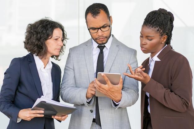Grupo empresarial serio que lee y discute el informe del proyecto