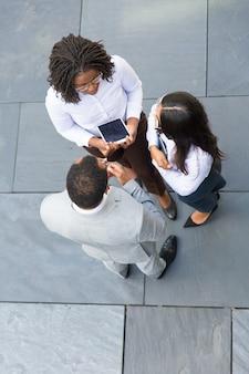 Grupo empresarial de tres hablando cerca de la oficina