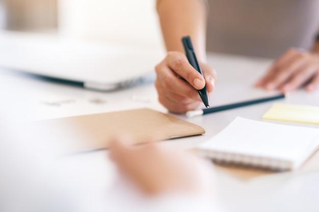 Grupo de empresario discutiendo y escribiendo en el cuaderno sobre la mesa en la oficina