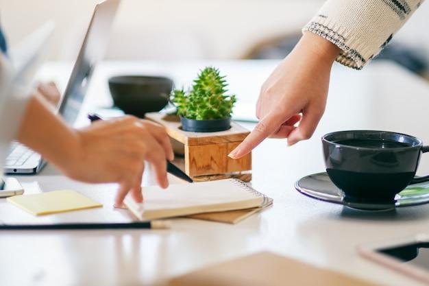 Grupo de empresario discutiendo, escribiendo y señalando con el dedo en el cuaderno sobre la mesa en la oficina