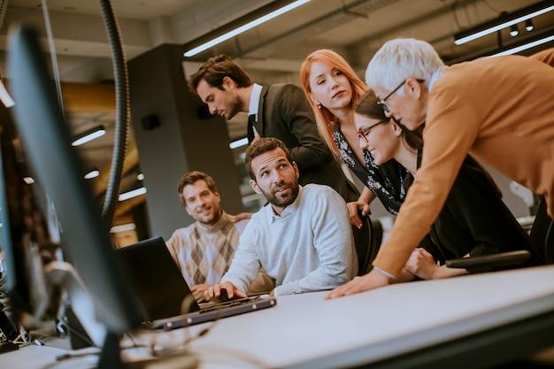 Grupo de empresarios con adultos jóvenes y colega senior en reunión en el interior de la oficina moderna brillante