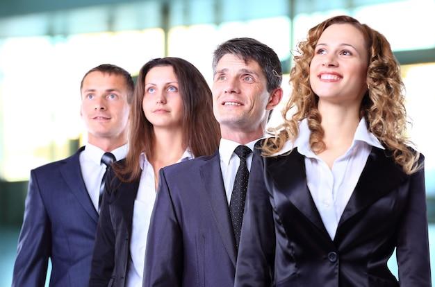 Grupo de empresarios amigables con feliz líder femenina en frente