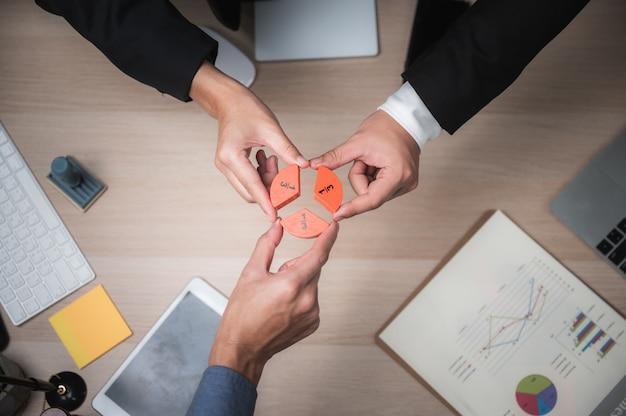Grupo de empresarios armando rompecabezas y representan el concepto de ayuda y ayuda del equipo