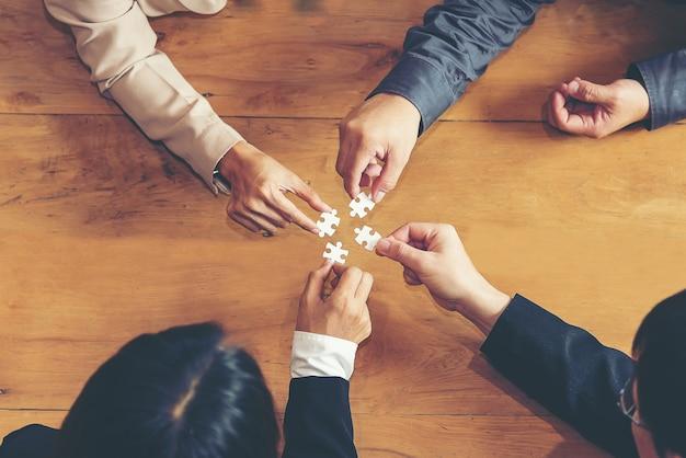 Grupo de empresarios armar rompecabezas y representar el apoyo del equipo y el concepto de ayuda, busin