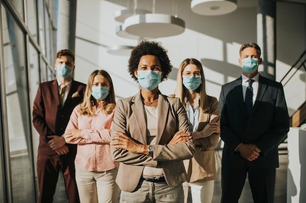 Grupo de empresarios asiáticos de pie en la oficina y usar una máscara para proteger prevenir la infección por el virus corona