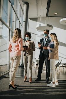 Grupo de empresarios asiáticos que se reúnen y trabajan en la oficina y usan una máscara para proteger y prevenir la infección por el virus corona