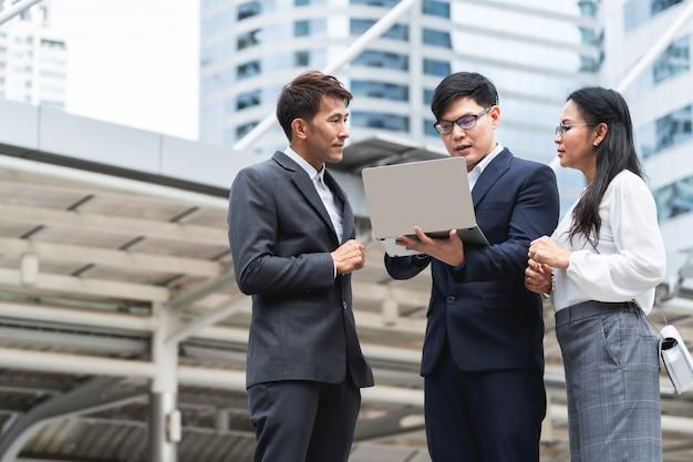 Grupo de empresarios asiáticos trabajando y discutiendo algo positivo con su colega maduro y usando una computadora portátil al aire libre en la capital