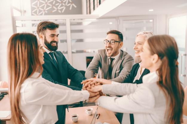 Grupo de empresarios corporativos alegres en ropa formal apilando las manos en la reunión en la sala de juntas.