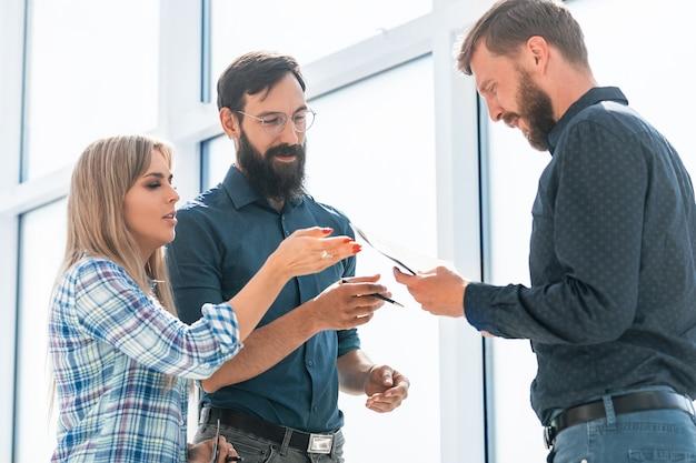Grupo de empresarios discutiendo documants de pie en la oficina