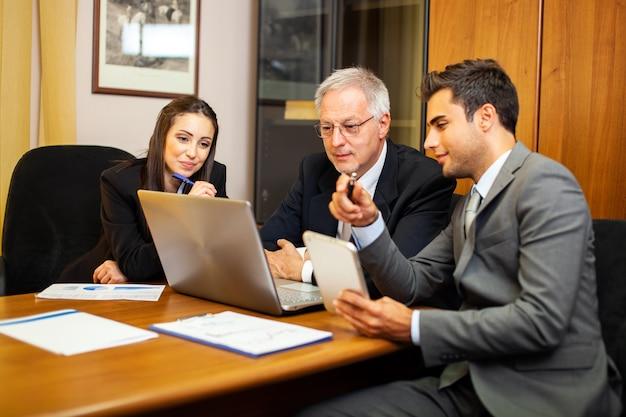 Grupo de empresarios discutiendo mientras mira la pantalla de un portátil