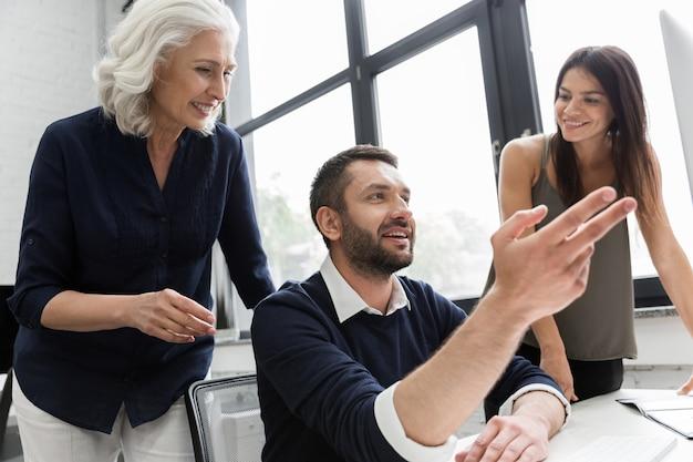 Grupo de empresarios discutiendo el plan financiero en la mesa en una oficina.