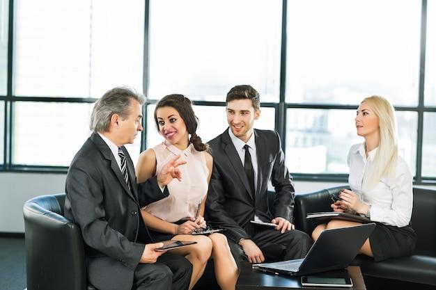 Un grupo de empresarios discutiendo la política de la empresa en la oficina.