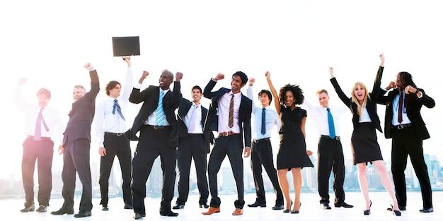 Grupo de empresarios diversos con los brazos levantados.