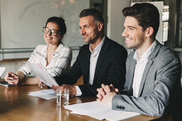Grupo de empresarios felices en trajes formales sentados a la mesa en la oficina y examinando el currículum vitae del nuevo personal durante la entrevista de trabajo - concepto de negocio, carrera y colocación