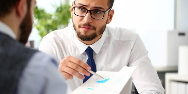 Grupo de empresarios con gráfica financiera y bolígrafo plateado
