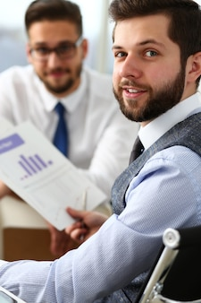Grupo de empresarios con gráfico financiero y bolígrafo plateado