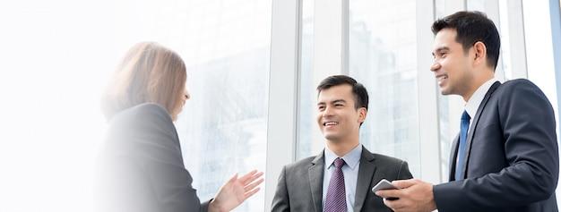 Grupo de empresarios hablando en el pasillo del edificio