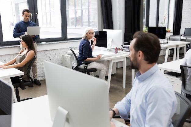 Grupo de empresarios hablando entre sí mientras trabajan