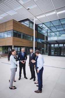 Grupo de empresarios interactuando fuera del edificio de oficinas