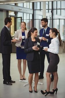 Grupo de empresarios interactuando entre sí en el vestíbulo