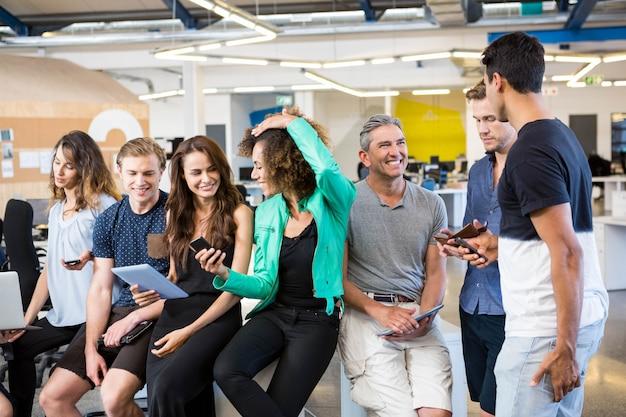 Grupo de empresarios interactuando durante el tiempo de descanso en la oficina