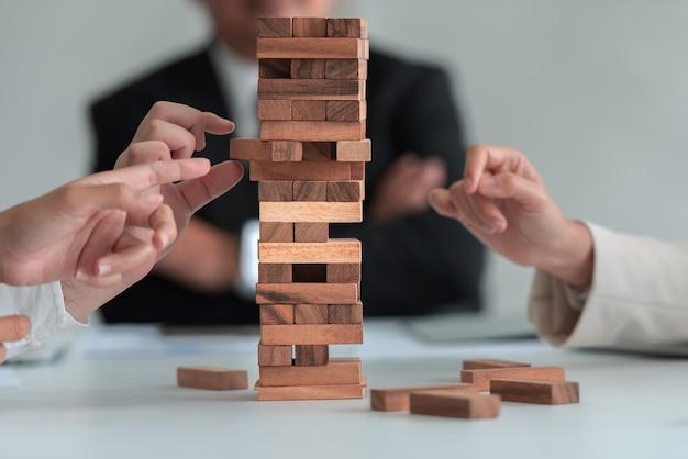 Grupo de empresarios jugando bloques de madera del juego, creación de empresas, riesgo y crecimiento.