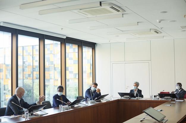Grupo de empresarios con máscaras protectoras sentados a la mesa durante la conferencia en la sala de juntas