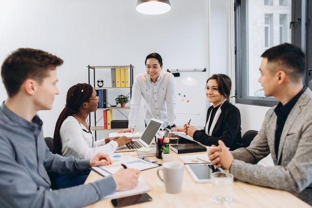 Grupo de empresarios multiculturales escuchando su discurso de jefe, gerente de hombre asiático hablando con su equipo