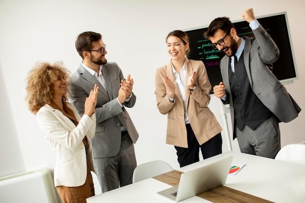 Grupo de empresarios multiétnicos aplaudiendo después de una reunión exitosa en la oficina