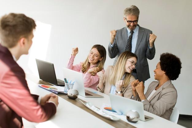 Grupo de empresarios multiétnicos escuchan buenas noticias mientras trabajan en un nuevo proyecto
