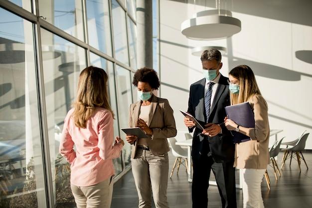 Un grupo de empresarios multiétnicos tiene una reunión y trabaja en la oficina mientras usa una máscara como protección contra el coronavirus