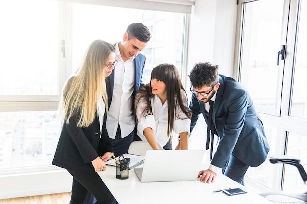 Grupo de empresarios de pie en la oficina mirando portátil en la oficina