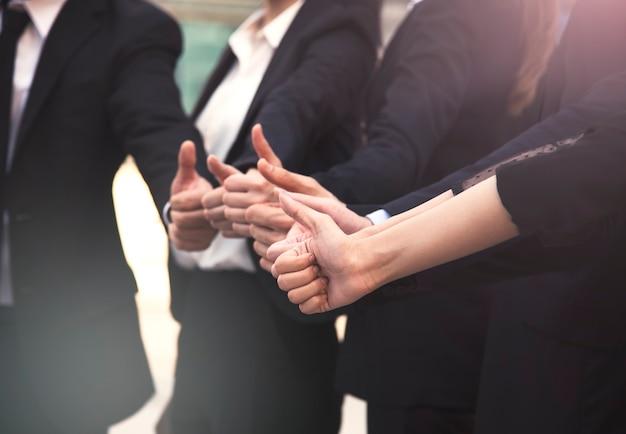 Grupo de empresarios pulgares arriba juntos. concepto de trabajo en equipo y éxito.