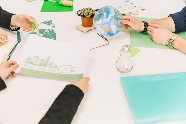 Grupo de empresarios que trabajan en el ahorro de energía sobre el escritorio