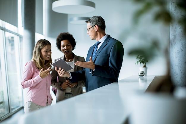Grupo de empresarios con tableta digital en reunión en la oficina