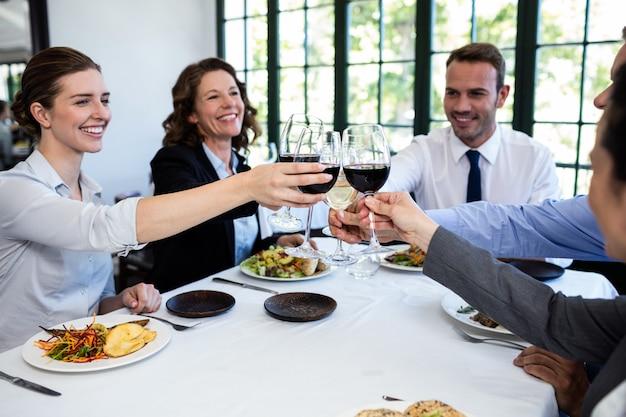 Grupo de empresarios tostado copa de vino durante la reunión de almuerzo de negocios