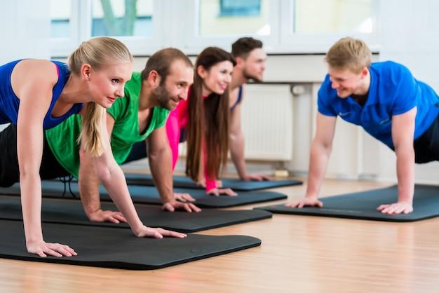 Grupo de entrenamiento en gimnasio durante fisioterapia.