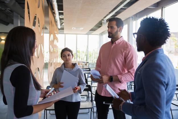 Grupo de entrenamiento multiétnico discutiendo su tarea