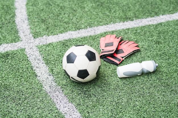 Grupo de equipo deportivo: balón de fútbol, guantes de cuero y botella de agua de plástico en el campo de fútbol verde