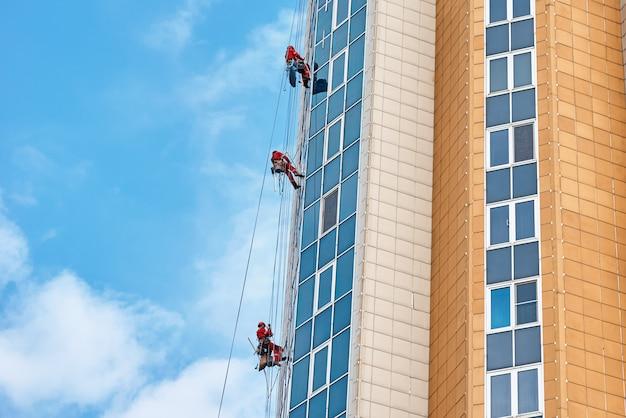 Grupo de escaladores industriales trabajan en un moderno edificio al aire libre