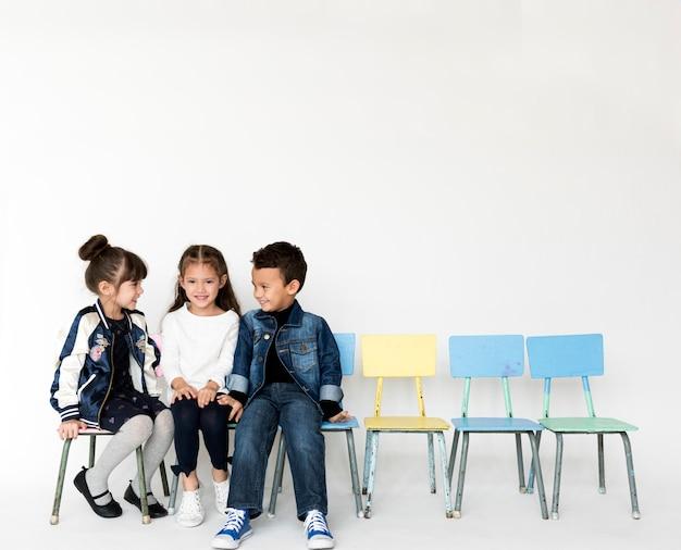 Grupo de escolares hablando juntos sonriendo sobre fondo blanco