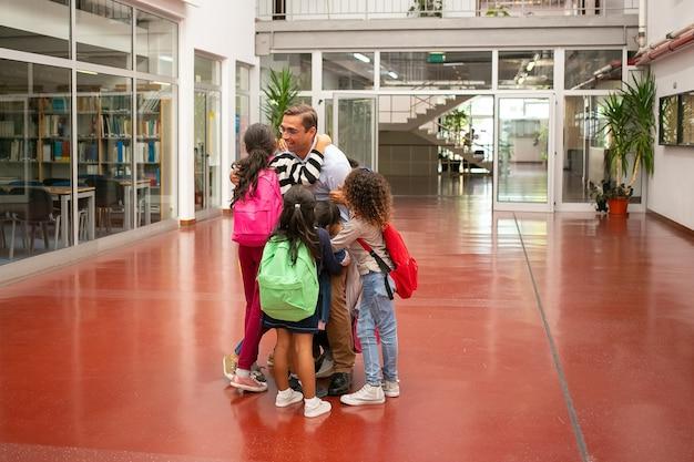 Grupo de escolares con mochilas brillantes, reunión y abrazos de maestro favorito en el pasillo de la escuela